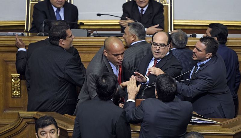 Newly elected opposition deputy Julio Borges (C) and governement deputy Hector Rodriguez (2nd L) argue during the  new parliament's swearing-in ceremony in Caracas, on January 5, 2016.  Venezuela's President Nicolas Maduro ordered the security forces to ensure the swearing-in of a new opposition-dominated legislature passes off peacefully Tuesday, after calls for rallies raised fears of unrest. AFP PHOTO/JUAN BARRETO