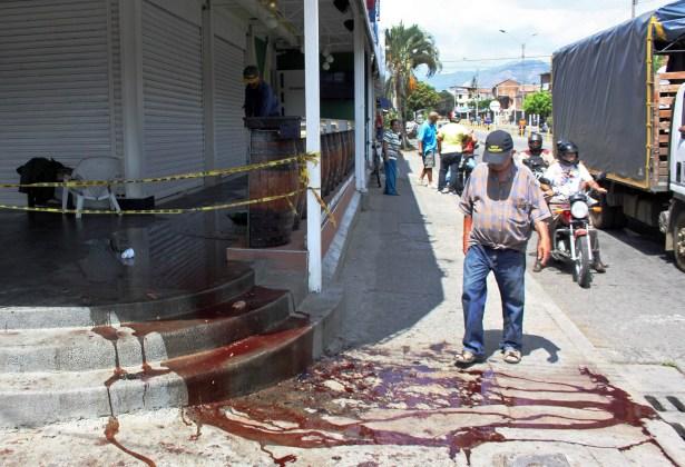Un transeúnte camina sobre una mezcla de agua y sangre en la acera junto al club La Barra de la 44 en Cali, Colombia, el sábado, 9 de noviembre del 2013. Ocho personas murieron y seis resultaron heridas el viernes por la noche en una balacera en el club. (Foto AP/Juan Bautista Diaz)