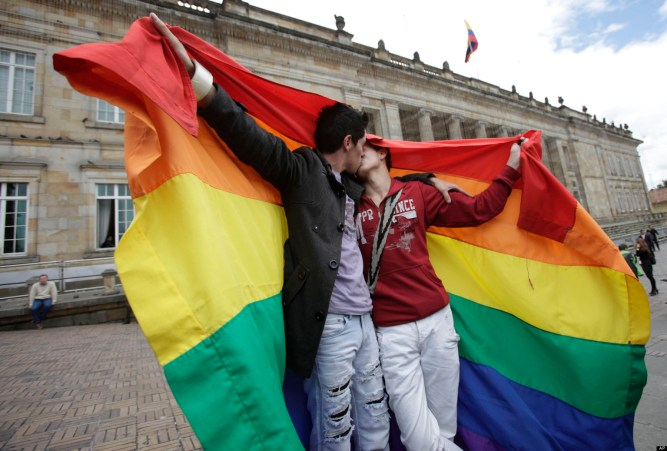 LGBT activists kiss in front of Colombia's Congress building to show support for a proposed bill to legalize same sex marriage, being debating on by legislators, in Bogota, Tuesday, Nov. 27, 2012. (AP Photo/Fernando Vergara)