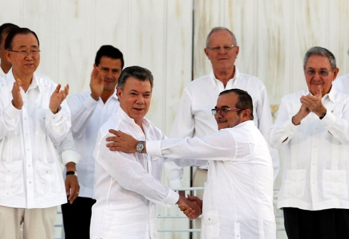 Colombian President Juan Manuel Santos (L) and Marxist rebel leader Rodrigo Londono (R), better known by the nom de guerre Timochenko, shake hands after signing an accord ending a half-century war that killed a quarter of a million people in Cartagena, Colombia September 26, 2016. REUTERS/John Vizcaino