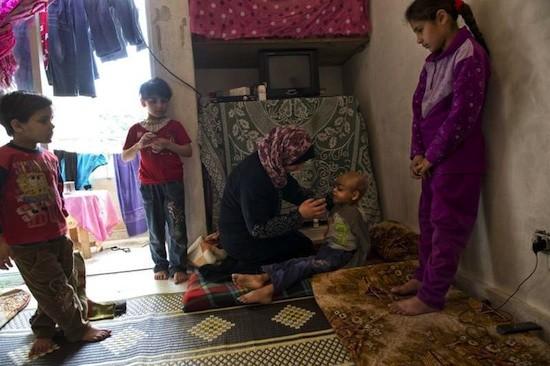 Una refugiada siria ofrece agua a su hijo, que padece un cáncer en fase terminal. La llegada de un número tan elevado de refugiados sirios está llevando al límite de su capacidad a los servicios de salud del Líbano.