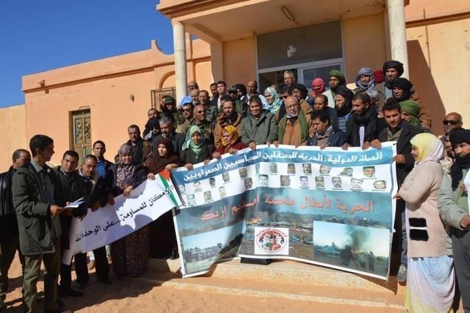 Periodistas saharauis despliegan pancarta de solidaridad con los presos del campamento Gdeim Izik.