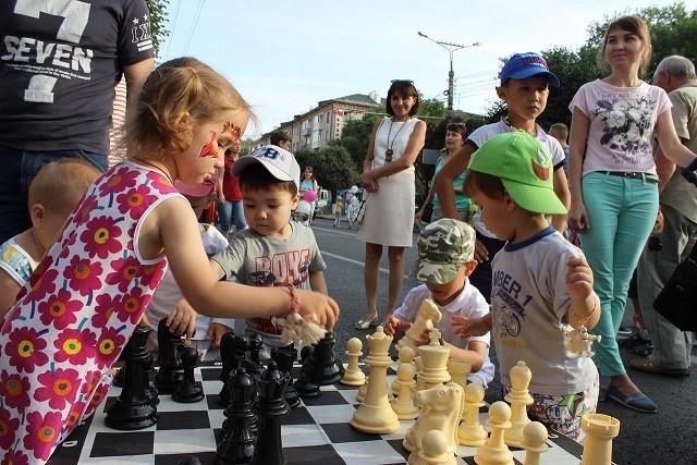 Niños rusos juegan una partida de ajedrez al aire libre.