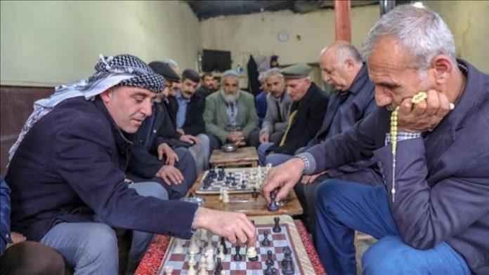 Dos personas juegan al ajedrez, el de la derecha sostiene un tasbih, rosario musulmán