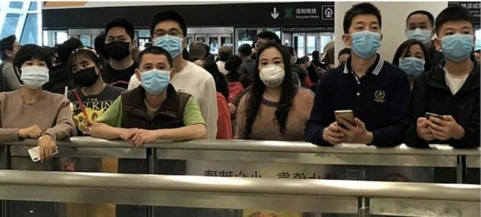 ONU: Gente con mascarillas para protegerse del coronavirus espera en la zona de llegadas del aeropuerto internacional de Shenzhen Bao'an.