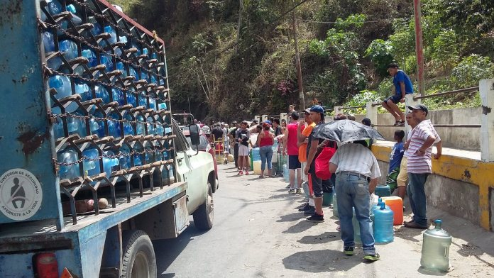 La escasez de agua en Caracas continúa forzando a habitantes de las barriadas populares a formar largas filas para llenar unos pocos bidones en algunas tomas a orillas de las vías. Comprar agua de garrafones resulta cada vez más costoso en medio de la profunda crisis socioeconómica en que está hundida Venezuela. Foto: Humberto Márquez /IPS
