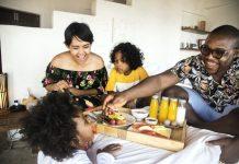 Familia africana desayuna en la cama