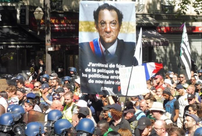Julio Feo: manifestación en París, 14 de agosto de 2021. En cabeza un retrato de Coluche: «Dejaré de hacer política cuando los políticos dejen de hacernos reír». La palabra reír está reemplazada por «miedo», ….dejen de darnos miedo…