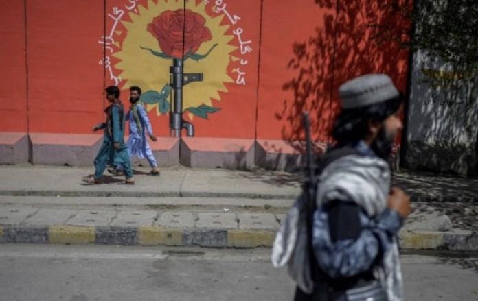 Un combatiente talibán pasa junto a un mural en una calle de Kabul el 15 de septiembre de 2021. © Bulent Kilic AFP FIP