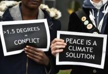 Activistas en Francia sostienen carteles en los que piden una solución para reducir las temperaturas a 1,5°. Foto: ANDES/AFP