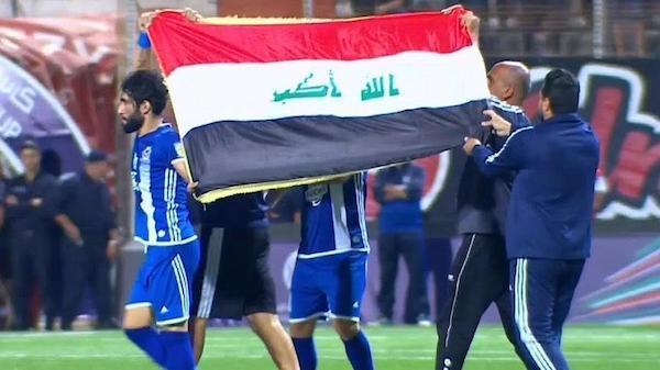 El equipo del Club Athletic Fuerzas Aéreas (Nadi Al Quwa Al Jawiya Al Riyadhi) de Bagdad muestra su bandera al abandonar el campo de juego en Argel