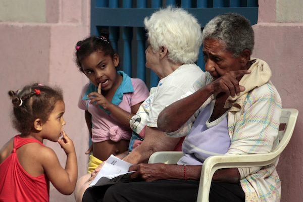 Dos abuelas con sus nietas a las que cuidan mientras sus madres trabajan, en una calle del casco histórico de la Habana Vieja, en Cuba. Los abuelos y abuelas trabajadores son incluidos en los beneficios de las nuevas normas para estimular la maternidad. Crédito: Jorge Luis Baños/IPS