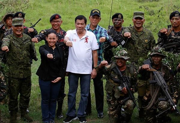 """Roberto Duterte hace su gesto de campaña de """"puño de hierro"""" rodeado de soldados."""