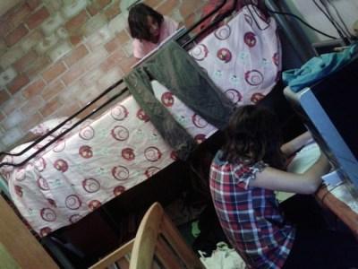 Estefanía lee en la litera mientras Encarni hace las tareas escolares, acodada sobre una mesa de su pequeña habitación. Esta niña malagueña de 12 años es uno de los rostros de la pobreza infantil en España, que según un nuevo informe de Unicef afecta a 36,3 por ciento de ese sector de la población. Crédito: Inés Benítez/IPS