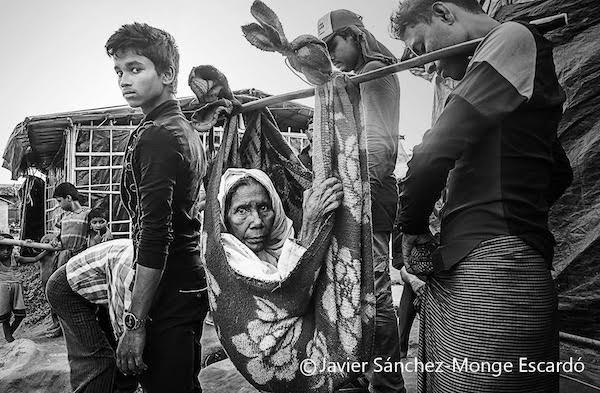 9/NOV/2017. Campo de refugiados de Lita: Traslado de una anciana Con ayuda de un miembro de su familia y de otros rohinyás, una anciana enferma es trasladada a una clínica. Existe una encomiable unidad entre los rohinyás, y su conciencia de grupo les hace ayudarse los unos a los otros, lo que ha posibilitado que muchos de los que habían caído heridos en Birmania, pudieran llegar a Bangladesh al ser ayudados por los demás y ello a pesar de que a veces supusiera un grandísimo esfuerzo ya que todos se encontraban débiles y sin alimentos ni equipaje alguno. La vida de los más jóvenes y de los más ancianos en los campos se hace sumamente difícil.