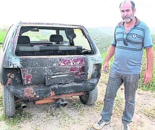 Joao Miranda Do Carmo junto a su vehículo incendiado en 2014