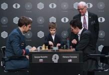 Inicio de la partida decisiva entre Karjakin y Caruana, con presencia del árbitro y un niño que pone en marcha el reloj.