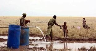 Un policía keniata da agua potable a un niño sediento en el pozo de la villa de Lotikipi.
