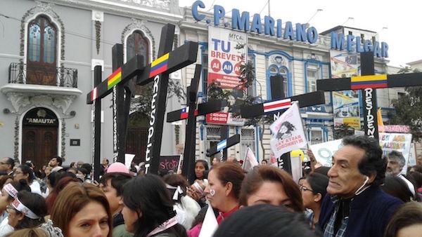 """Un grupo de manifestantes con cruces negras, simbolizando las víctimas de feminicidio en Perú y otros países latinoamericanos, pasan por una calle del centro de Lima, durante la multitudinaria marcha celebrada el 13 de agosto bajo la consigna """"Ni Una Menos"""". Crédito: Noemí Melgarejo/IPS"""