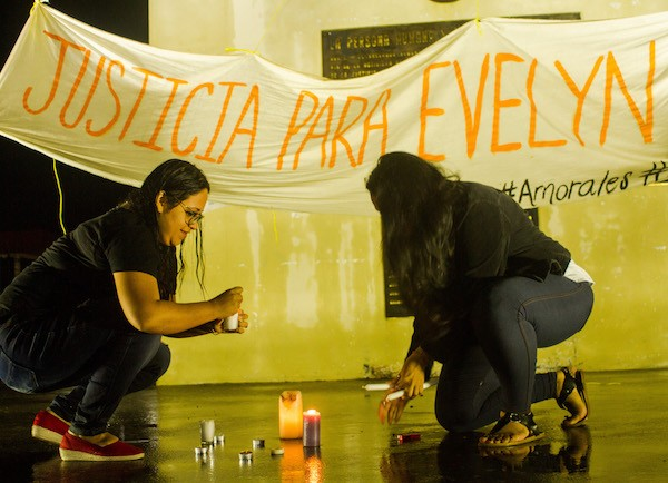 Dos mujeres prenden velas ante el monumento a la Constitución, en la capital de El Salvador, durante una manifestación de protesta la noche del 10 julio, contra la condena a 30 años de cárcel de la joven Evelyn Hernández, acusada de haberse practicado un aborto. Crédito: Edgardo Ayala/IPS
