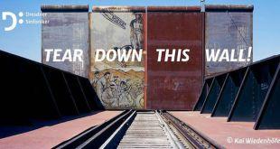 Cartel del concierto de la Orquesta Sinfónica de Dresde ante el muro que separa EE. UU. de México