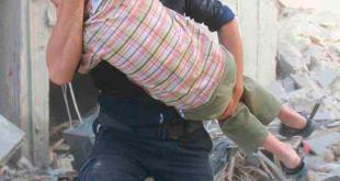 Un voluntario de los cascos blancos ayuda a un niño herido en un bombardeo