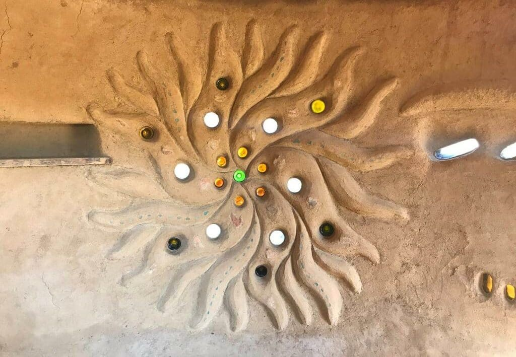 cob sculpture in a natural building, with bottle bricks and stone ornaments, plastered