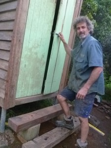 Tom walking up the steps to enter the compost toilet outhouse