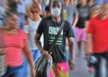 A man wearing a face mask as a precautionary measure against the spread of the new coronavirus, COVID-19, arrives during rush hour at Rio de Janeiro's Central train station, in Brazil, on March 16, 2020. (Photo by Carl DE SOUZA / AFP)