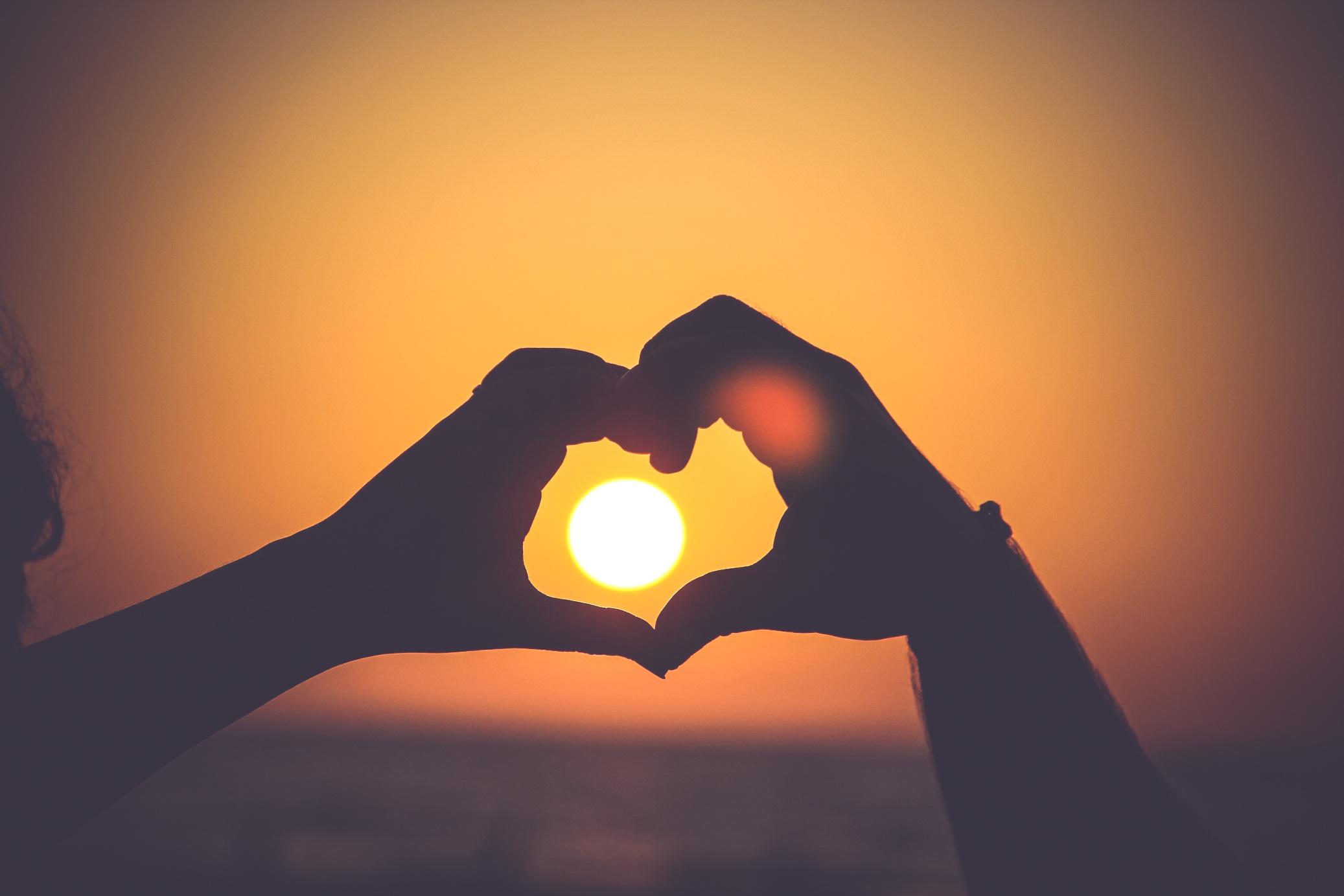 Hands making a heart in front of a sun from Unsplash.com - https://unsplash.com/mayurgala