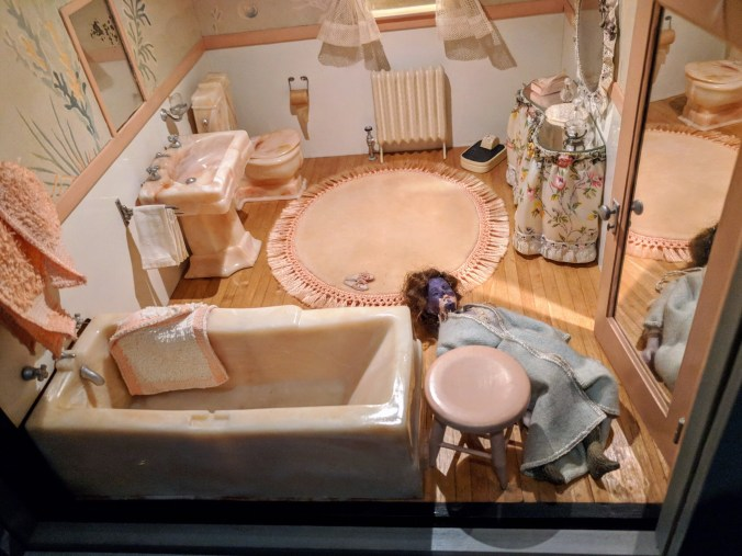 A doll lays dead on the floor of a bathroom.