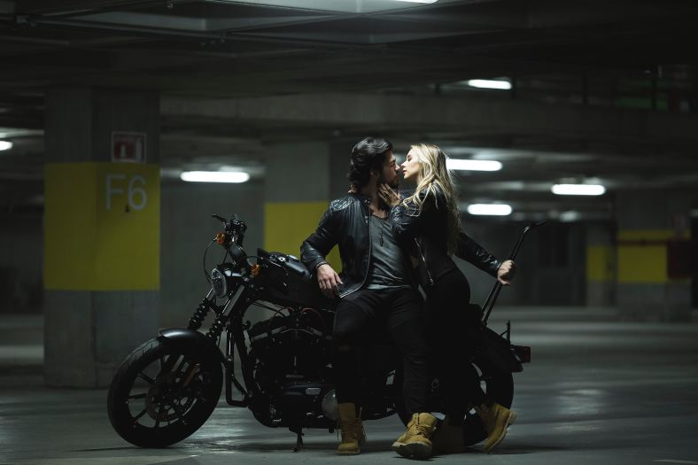 Man on motorcycle about to kiss blonde woman