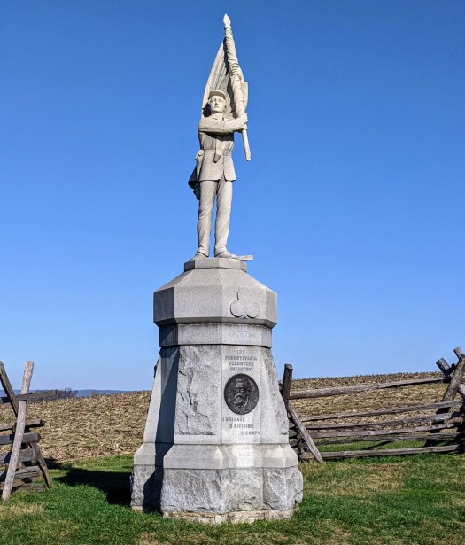 Statue of a young soldier holding a flag.