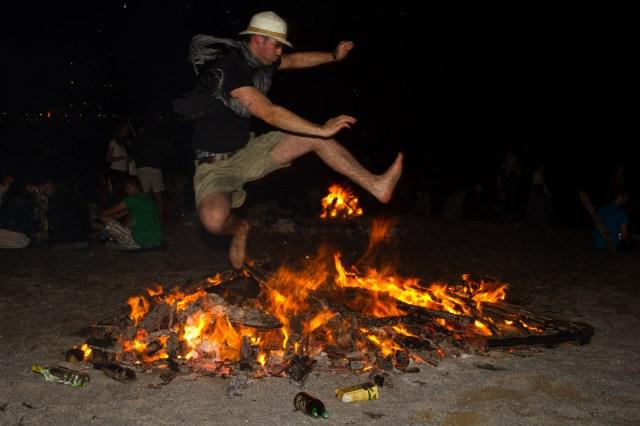 Saltando sobre una hoguera de San Juan para llamar a la buena suerte