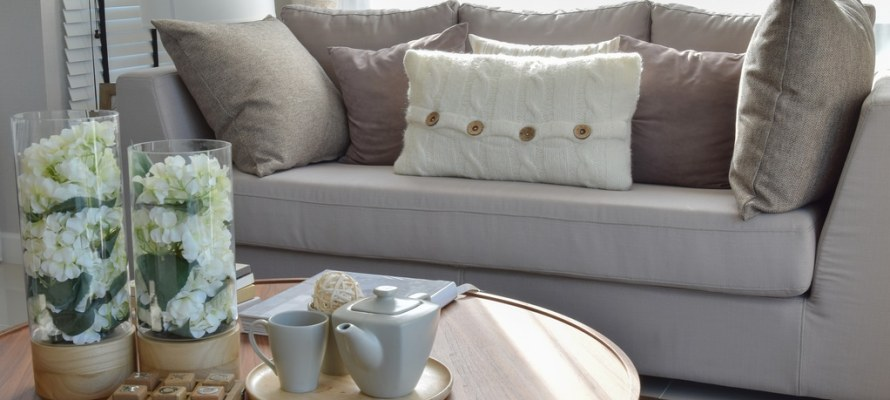 decorative tea set and glass vase on wooden round table in living room interior. Utah home builder.