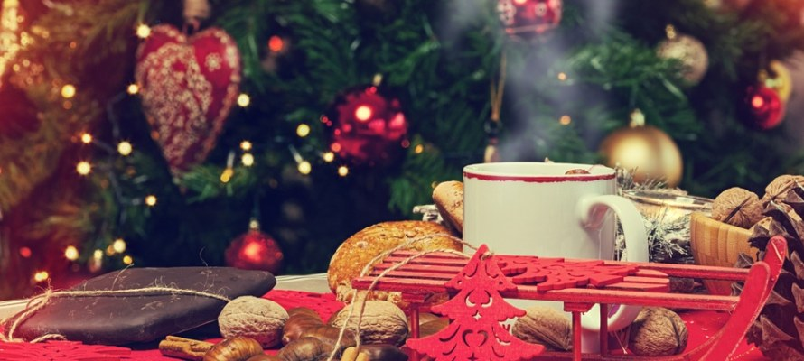 Cup of hot tea on Christmas table with behind christmas tree.