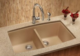 Under-mount, composite sink divided into to tubs with faucet and sprayer.