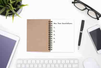 New year resolutions notebook on a white desk