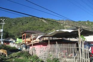 Rumah rumah sejajar pantai dengan bukit berkapur di belakangnya