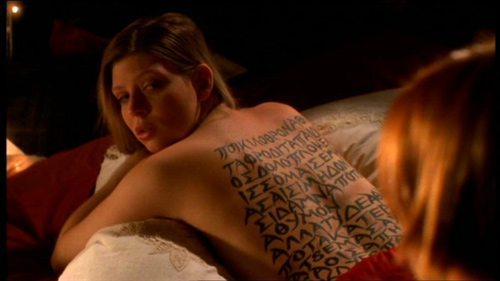 Tara with a poem written in Greek on her naked back