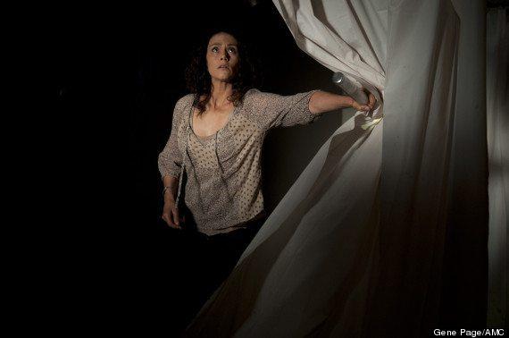 Karen pushes aside a shower curtain.