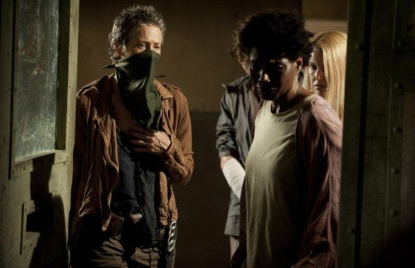 """Three people stand around the open door of a room in The Walking Dead 4.03 """"Isolation."""""""