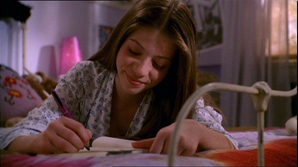 Dawn smiles as she writes in her journal.
