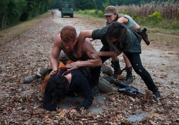 Glenn and Abraham fight in the road while Tara and Rosita try to separate them.