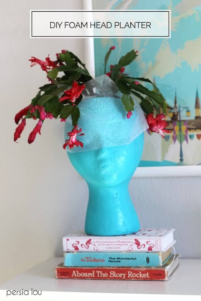 turquoise head shaped planter with pink christmas cactus