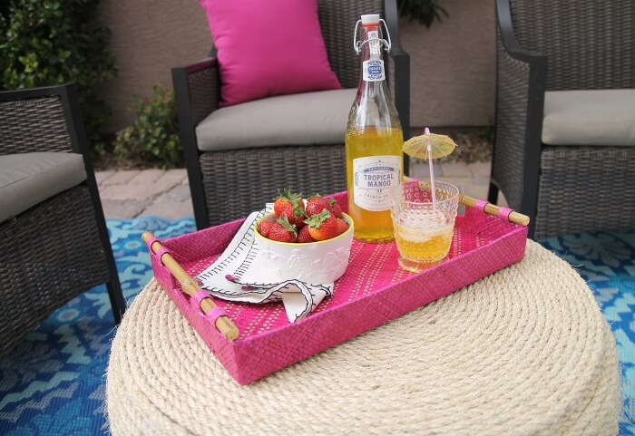 finished diy tire coffee table holding pink tray with fruit and drinks