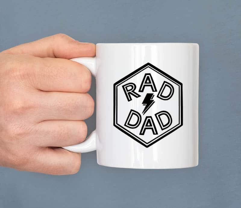 hand holding white mug showing rad dad hexagon cut file design