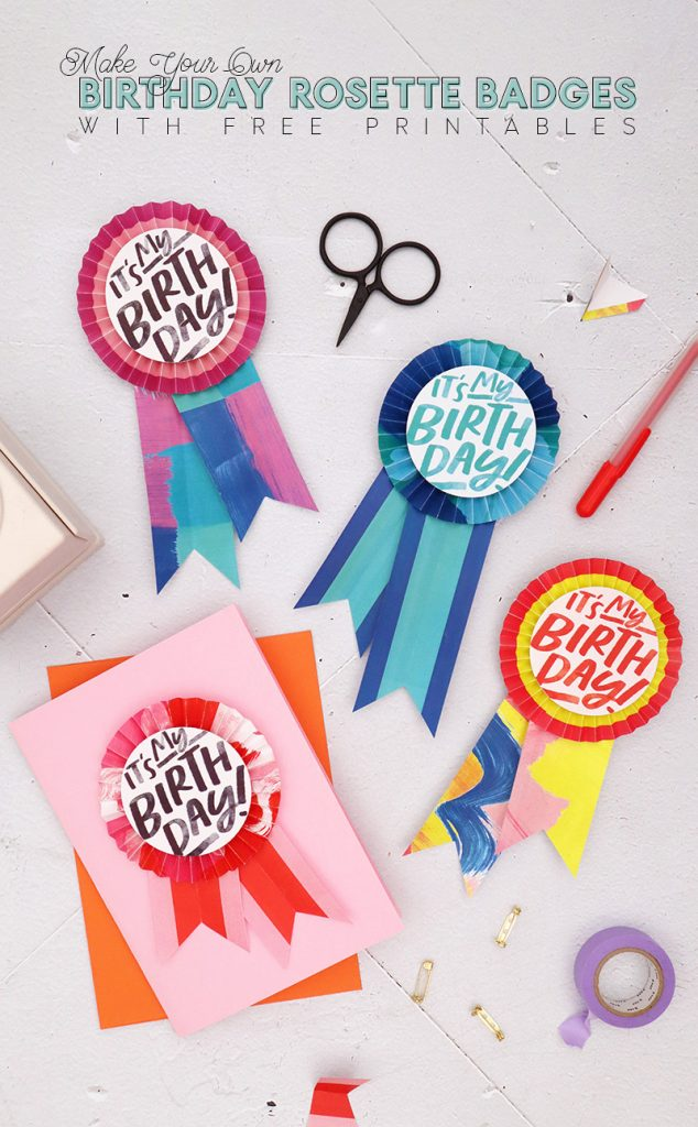 Colorful paper birthday buttons laying on a white background surrounded by scissors, pins, and a pen.