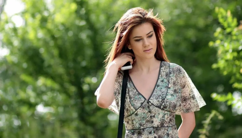 blog picture of young woman with cell phone touching her neck