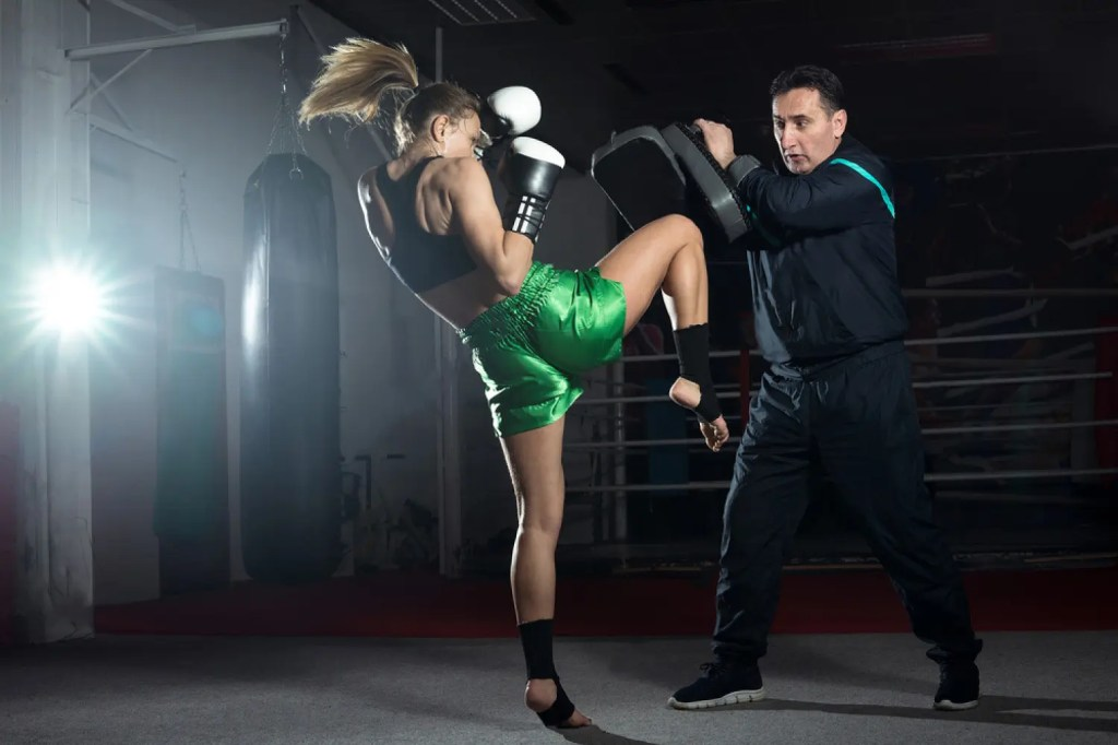 woman kick boxer works out with trainer
